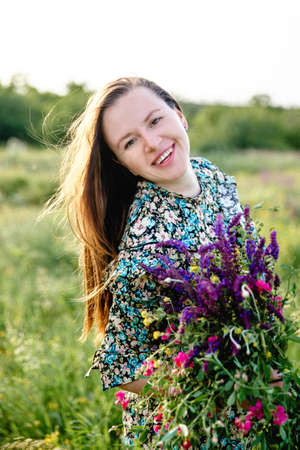 Portrait of a young beautiful long-haired blonde woman of European appearance with a blooming bouquet of wild flowers in her hands