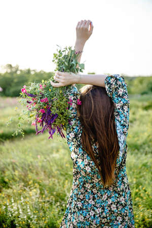 A young woman with long hair in a colorful short dress holds a bouquet of wild flowers in her raised hands while standing with her back to the camera