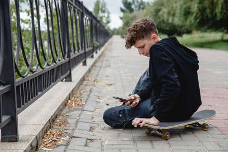A curly-haired teen of European appearance in black hoodie sitting on an alley on a skateboard and talking on the phone