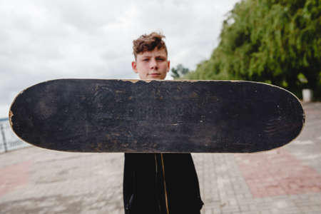 A curly-haired European teen holds a black old shabby skate in front of him. Only the skate is in focus. Space for text