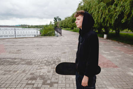 A curly-haired European teenager in a black hoodie with a skate in his hands stands on the embankment. Profile view