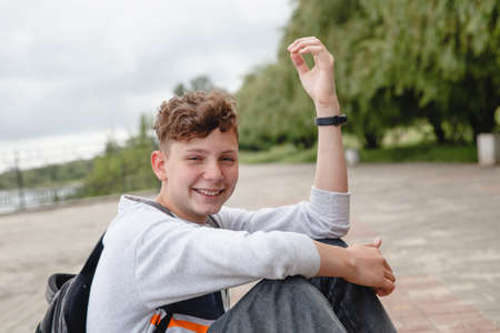 A curly-haired laughing European teen in a gray jumper, jeans and with a satchel on his back is sitting on the pavement