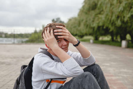 A curly-haired laughing European teenager in a gray jumper, jeans and with a satchel on his back is sitting on the pavement and covering his face with his hands