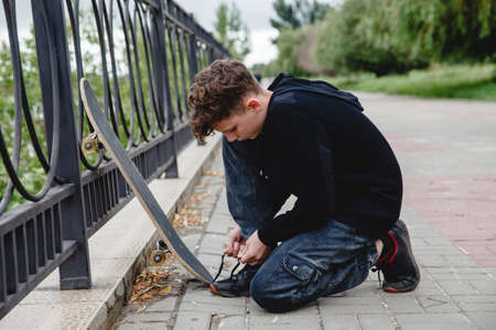 A curly-haired European teen in a black hoodie with skate sitting on the embankment and tying his shoelaces on sneakers