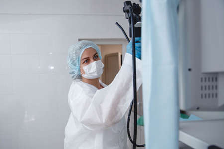 A young female endoscopist in a white protective suit, cap and gloves prepares the equipment for work. Stockfoto