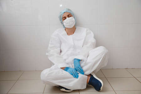 a young female doctor in a protective suit, cap, mask and gloves is sitting wearily on the floor Stockfoto