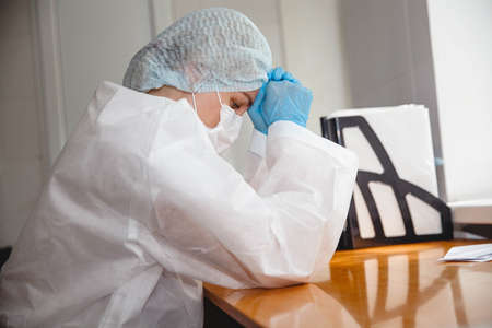 a young female doctor in a protective suit, cap, mask and gloves sits wearily at the table with her eyes closed