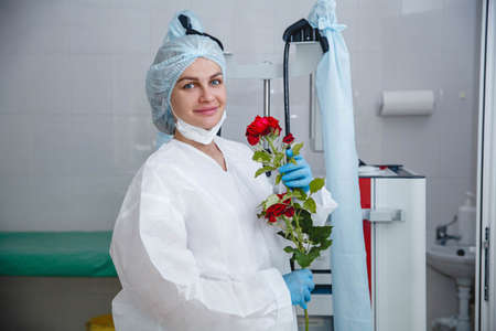 A young female doctor in a white protective suit, cap and gloves holds a red rose presented to her Stockfoto
