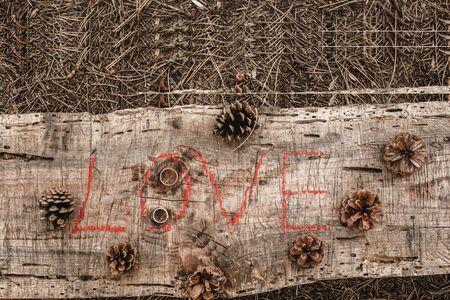 lipstick inscription love on a wooden Board. On the Board a few pine cones