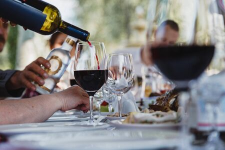 The process of pouring red wine into a glass. Public open air feast