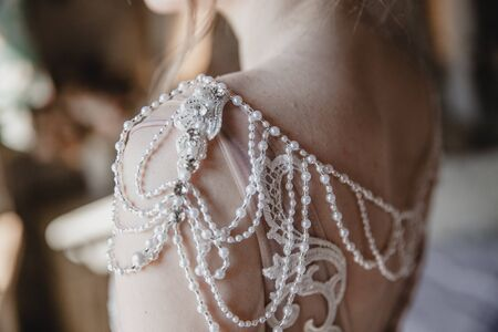Decorative elements of the wedding dress on the brides shoulders. Threads with pearl beads