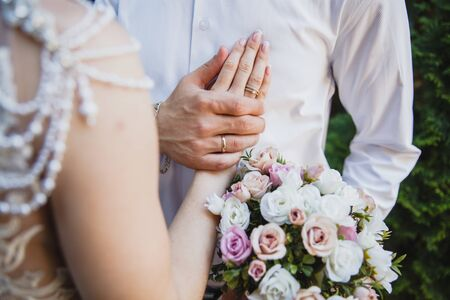 The groom holds the bride by the hand on his chest. There are wedding rings on their hands.