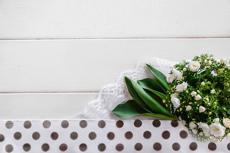 Bouquet with small white flowers, long green leaves, white lace, white polka dot fabric on a white wooden background. Flat layout with space for text Imagens