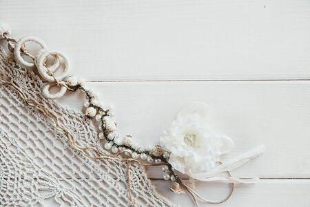 A piece of crocheted light tablecloth and flower costume jewelry on a white wooden background. Vintage background with space for text