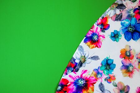 A patch of white fabric with multicolored flowers on a bright green background. Space for text Banco de Imagens
