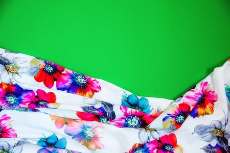 A patch of white fabric with multicolored flowers with drapery on a bright green background. Space for text