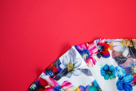 A patch of white fabric with multicolored flowers with drapery on a bright pink background. Space for text