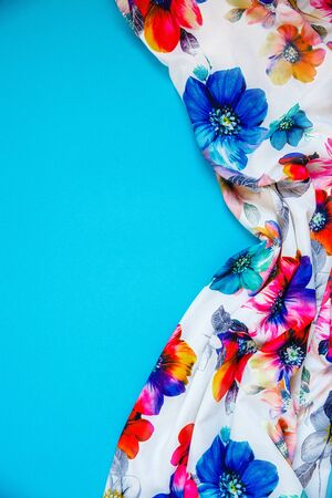A patch of white fabric with multicolored flowers with drapery on a bright blue background. Space for text