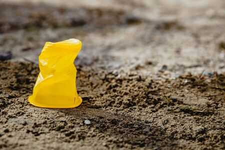One yellow crumpled plastic Cup standing on the ground. Global concept of environmental disaster