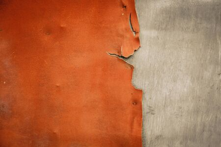 Pieces of old, worn leather with ragged edges on the charred wall. Background in retro style. Frayed texture in orange gray tones