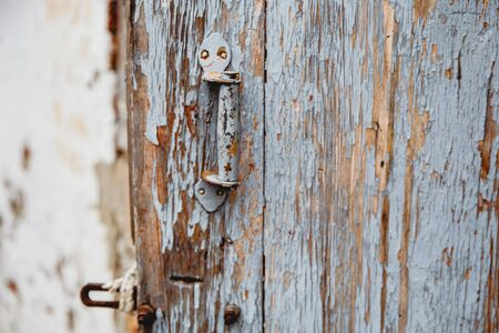 Old shebby wooden door with remnants of old paint. A handle is bolted to the door. Stock Photo