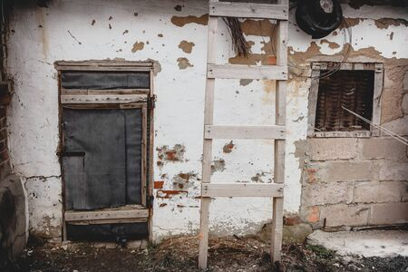 Old white wall of a house with peeling paint and an old closed door. Decrepit building. Retro. Stock Photo