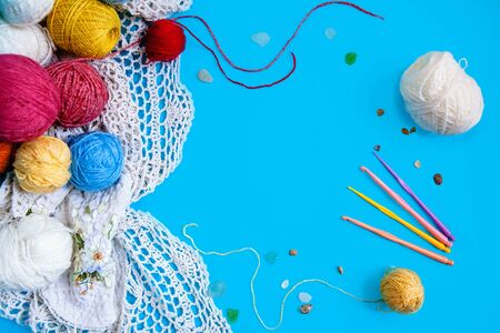 Scattered colored balls of thread , a white knitted tablecloth and colored hooks on a blue background. Flat layout with space for text