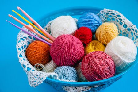 Basket with colorful balls of thread and hooks for knitting. Flat layout on a blue background. Close up. Stock Photo