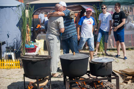 Fish soup festival in the South of Russia. Folk festivals and cooking fish soup. The atmosphere of hospitality and friendliness. Large vats of dry cooking over a fire Editorial