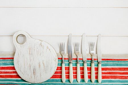 A round, battered cutting Board and antique eating utensils - knives and forks with bone handles. The Board and appliances lie on a striped towel on a white table. Flat layout with space for text 免版税图像
