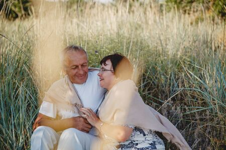An old married couple on a summer walk in the field. The couple sit hugging each other in the grass Imagens