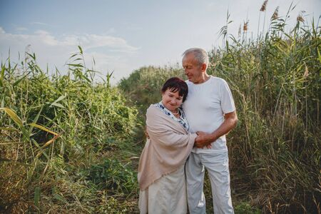 An old married couple on a summer walk in the field Imagens