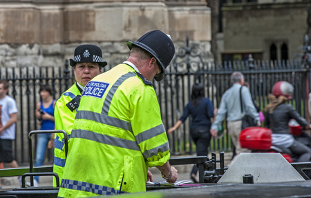 custodian: Two policemen London photographed in front of the Palace of Westminster on St  Margaret ST  A man and a woman from the London Metropolitan Police  The woman has a suspicious look