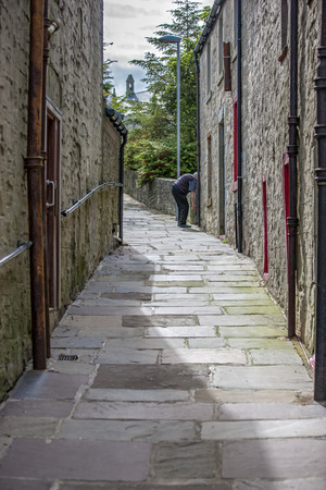 17th: Lerwick, Shetland, Scotland, United Kingdom. Street View of the old city of 400 years (17th century) with its characteristic granite houses in northern Europe. An passage with an old man at the end.