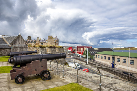 Lerwick, Shetland, Scotland, United Kingdom. Lerwick, Shetland, Scotland, United Kingdom. View of Two Cannon at Fort Charlotte, with  the city in the background
