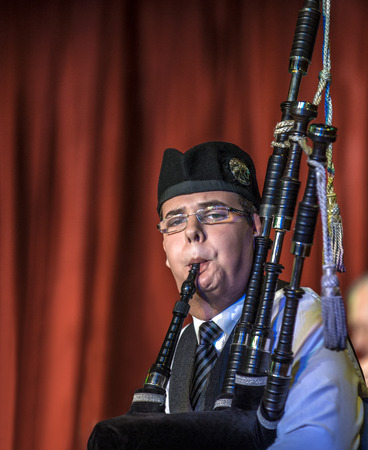 Scottish musicien bagpiper1 from a band acts as host upon arrival of transatlantic ships in the port of Invergordon in Scotland committee.  Editorial