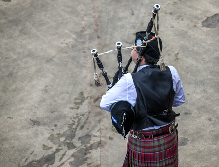 Scottish musicien bagpiper from a band acts as host upon arrival of transatlantic ships in the port of Invergordon in Scotland committee.  Editorial