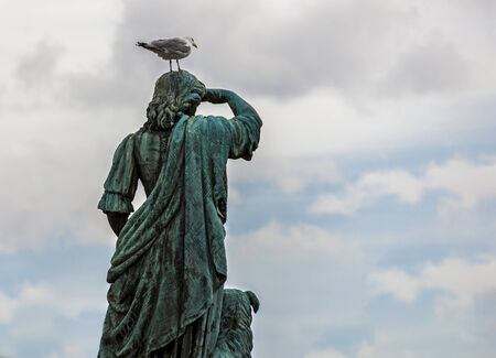 Statue of Flora Macdonald, seen from behind, with a seagull on his head. Stock Photo