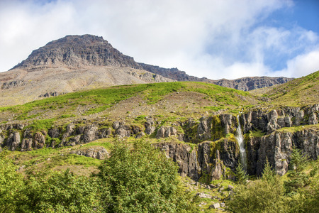 Rock mountain landscape with a waterfall near Seydisfjordur in Iceland Stock Photo
