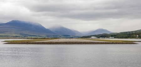 View from the end of runway at Akureyri airport in Iceland. A small plane is taking off.
