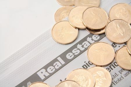 property: golden coin on the property section of a newspaper Stock Photo