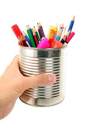isolated, hand holding a tin with color pencils photo