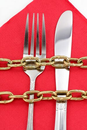 chain and fork with white background, concept of diet