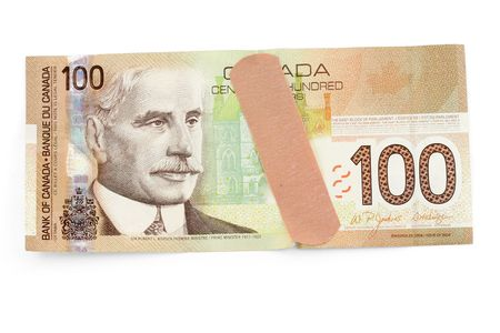 canadian currency: canadian dollar and bandage with white background