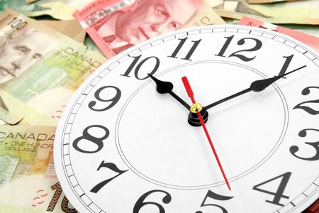 canadian cash: wall clock and canadian dollars, concept of time is money Stock Photo