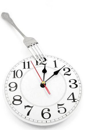 白い背景と、昼食の時間の概念とフォークと壁時計 写真素材
