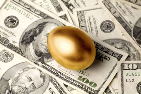 priceless: golden egg and dollars, concept of Making Money Stock Photo