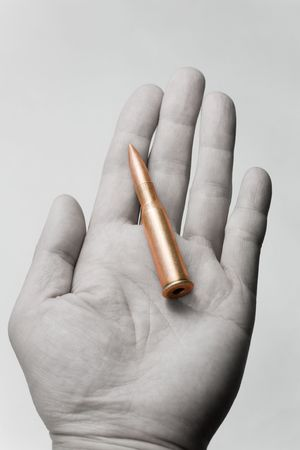 crime: hand holding a Rifle Bullet, concept of terrorism, blackmail, crime Stock Photo