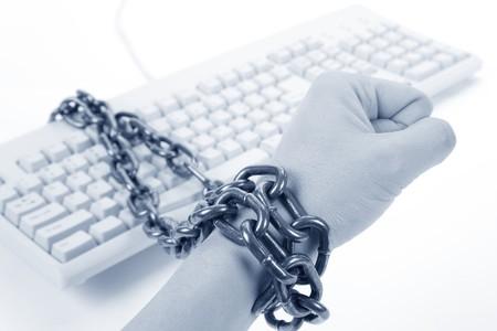 手はコンピューターのキーボードと鎖によって縛らアップされていた 写真素材