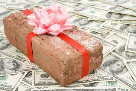 prank: Red Brick Gift and dollars, Concept of joke, make fun of somebody, gift on April Fools Day, Prank gift